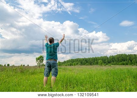 a young man rising hands to sky