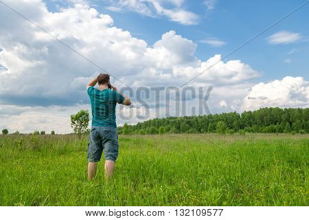 man standing in a field and talking on the phone