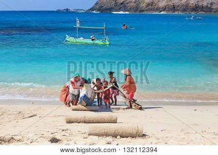 MAWUM BAY FISHER VILLAGE LOMBOK ISLAND INDONESIA - OCTOBER 17 2014 Local children help parents to drag out traditional fisherman boat from turquoise ocean water surf to white sand beach.