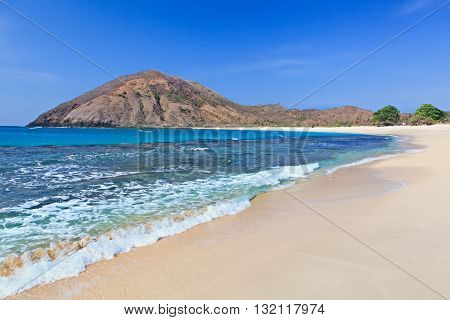 Tranquil scene on best desert beach with white sand clear water on ocean bay Mawun in tropical island Lombok. Boundless tropic beach with no people in lost paradise. Travel and vacations in Indonesia