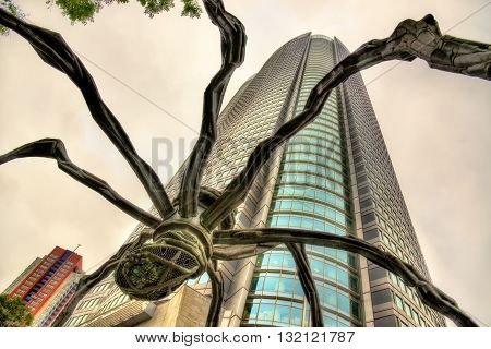 Tokyo, Japan - May 10, 2016: Maman, a spider sculpture, and Mori Tower in Roppongi Hills.