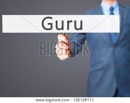 Guru - Businessman Hand Holding Sign
