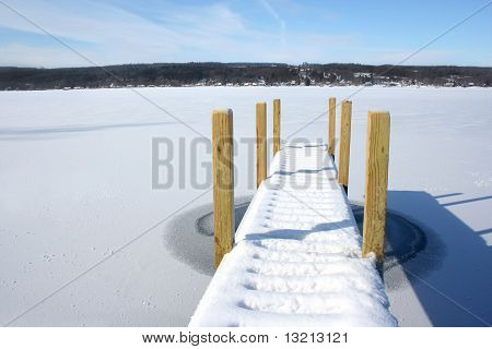 Snow covered pier on frozen lake