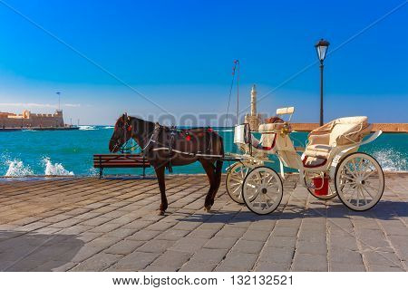 Horse carriage and Lighthouse in old harbour of Chania on a summer sunny day, Crete, Greece