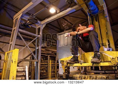 Exhausted factory worker smoking