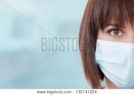Close-up of half face and right eye of woman doctor with mask against blue background with text area