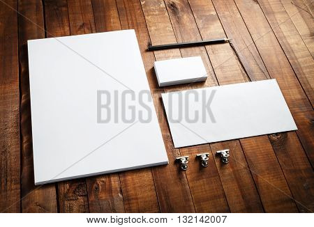 Blank stationery and corporate identity set on vintage wooden table background: letterhead business cards envelope and pencil. Blank mock-up for design portfolios.
