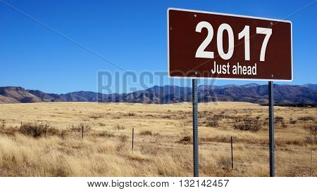 2017 Just Ahead brown road sign with blue sky and wilderness