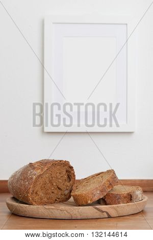 Bread on table empty picture frame on wall in background stock picture