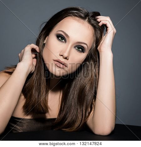 Fashionable woman. Beautiful female face. Woman of high society. Heartbreaker. Temptress. Seductive woman. Portrait of amazing young fashion woman posing at studio.