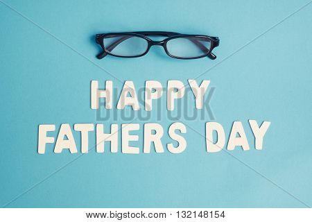 Happy Father's Day - Top view of white Happy Father's Day wording with black eye glasses on light blue background - Happy Father's Day pastel color