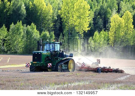 SALO FINLAND - MAY 27 2016: John Deere 9520T agricultural crawler tractor and cultivator on field at spring in South of Finland.
