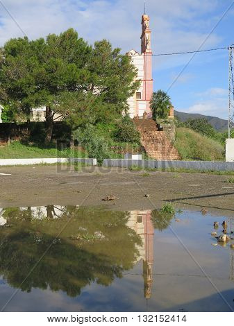 Belfry of Flores convent reflected in large rainwater puddle near Alora Andalusia