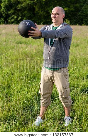 Man Exercising With 3 Kilos Medicine Ball Outdoors