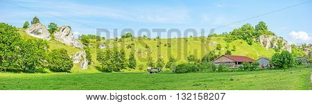 Rural panorama - farm at the impressive rocks of valley Eselsburger Tal near river Brenz - jewel of the swabian alps meadow in front