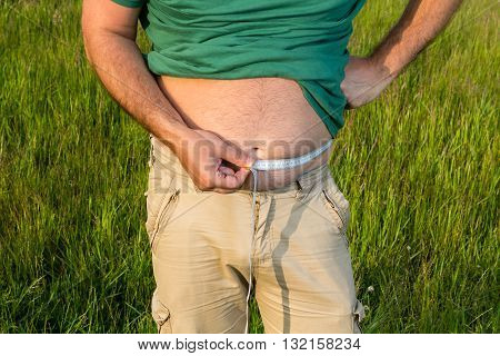 Man With Obesity Measures The Waist Circumference