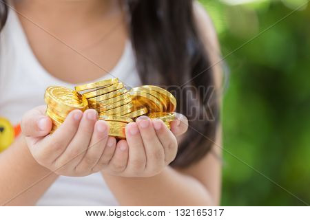 Hand holding golden coins concept on green background. Taxpayer business concept