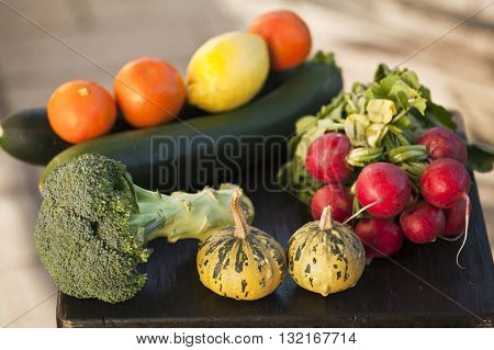 Group of fresh fruits: mandarines tangerines clementines lemons and vegetables: broccoli courgettes radish paprica and tomatoes on a wooden table