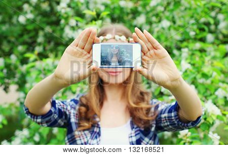 Woman Makes Self Portrait On Smartphone View Of Screen In Spring Flowering Garden