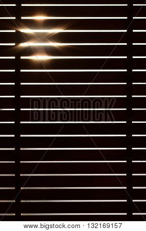 Wooden blinds in the interior of the home. Sun rays.