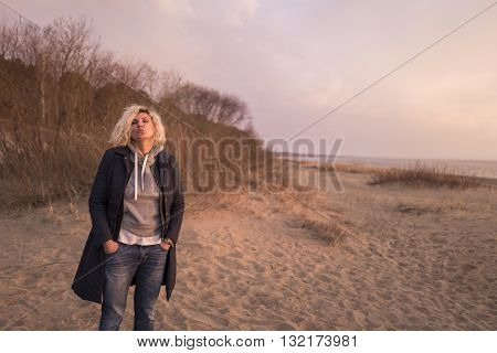 Beautiful blondie woman with curly hair is standing on the winter beach and sending a kiss to photographer