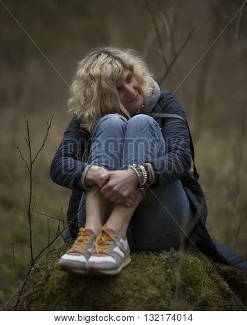 Blondie girl is seating on the stump in the forest the same as picture