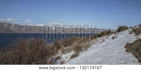 Panoramic view of Sevan Lake with snow maintains around of it