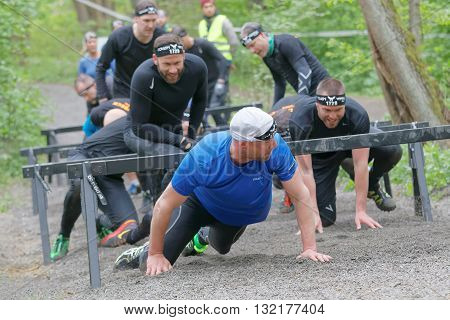 STOCKHOLM SWEDEN - MAY 14 2016: Group of smiling struggling people crawling under bars in the obstacle race Tough Viking Event in Sweden April 14 2016