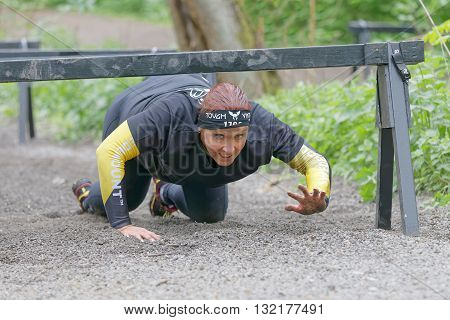 STOCKHOLM SWEDEN - MAY 14 2016: Struggling senior woman crawling under bars in the obstacle race Tough Viking Event in Sweden April 14 2016