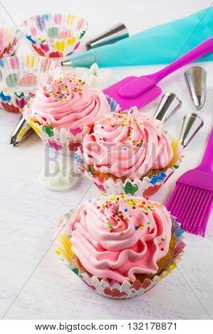 Pink cupcakes and kitchen utensils vertical. Birthday cupcakes. Homemade cupcake. Sweet dessert. Gourmet cupcakes. Sweet cupcake. Sweet pastry.