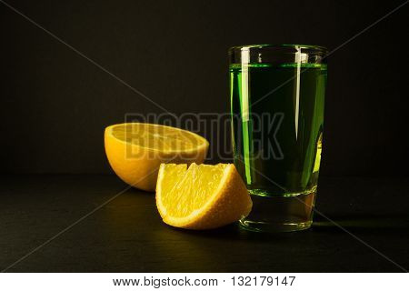 Absinthe and lime on black background. Alcohol drink. Green alcohol drink