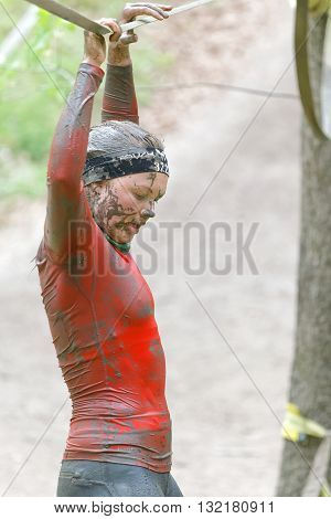 STOCKHOLM SWEDEN - MAY 14 2016: Woman with mud in her face trying to maintain her balance on a slack rope in the obstacle race Tough Viking Event in Sweden April 14 2016