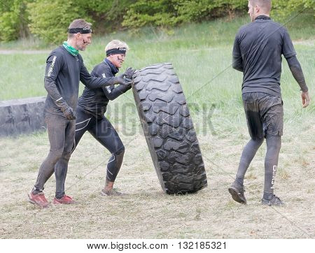 STOCKHOLM SWEDEN - MAY 14 2016: Two men struggling struggling to tip a large tractor tire obstacle in the obstacle race Tough Viking Event in Sweden April 14 2016
