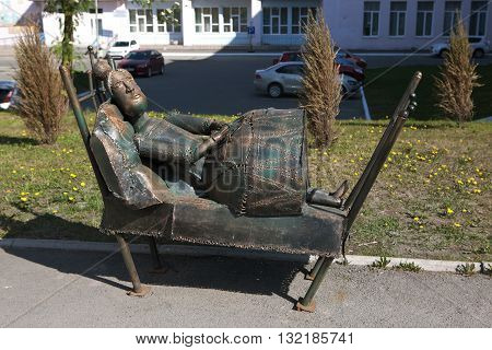 Sculpture of a woman lying on the bed.