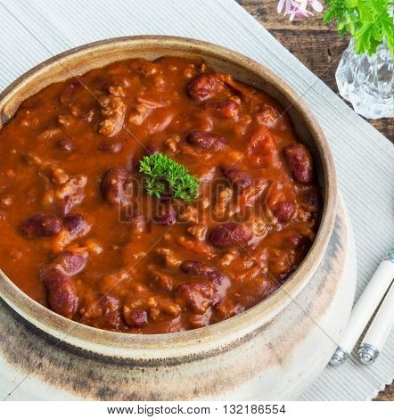Square overhead close shot of a meal of deep rich chilli con cane selective focus in a wooden table in a place setting