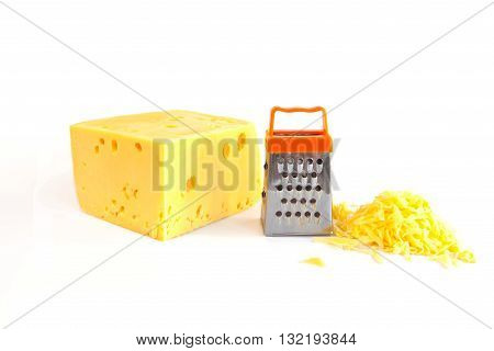 Piece of huge cheese grated cheese and small metal grate for preparing grated cheese isolated on white