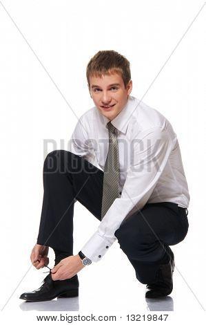 Businessman laces one's shoes