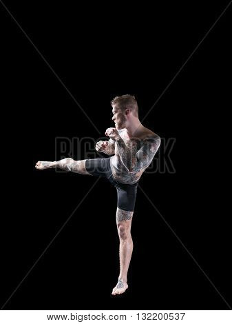 Young mma fighter trainig high kick on black background