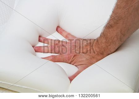 a male hand touching and testing mattress
