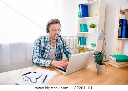Handsome Young Man In Headphones And Laptop Having Conversation