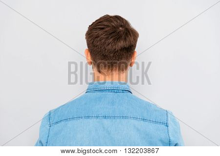 Back View Of Young Man Isolated On Gray Background