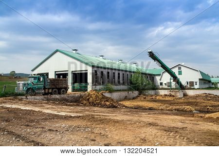 Dairy farm building exterior and manure pit in spring