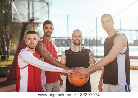 Team of basketball players holding a ball.