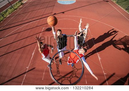 Team of basketball players playing basketball outdoors.