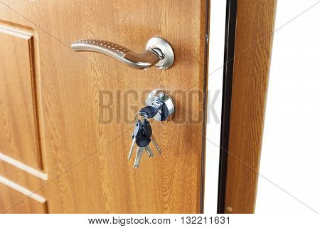 Open door handle wide angle. Door lock with keys. Brown wooden door closeup isolated. Modern interior design, door handle. New house concept. Real estate.