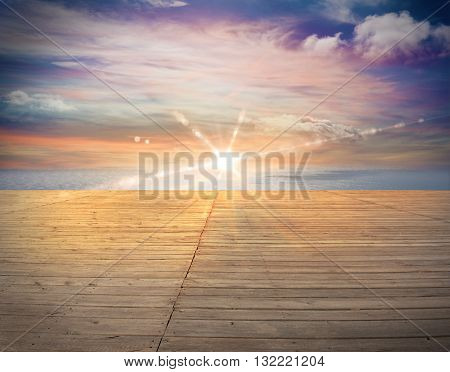 Wooden deck overlooking the ocean at sunset