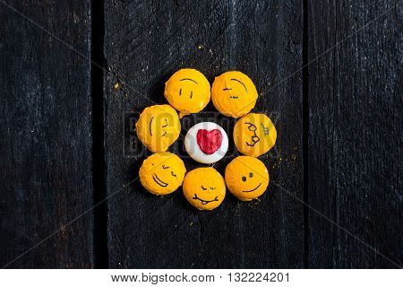 Some yelow pebble smile like a sun on black wood table. Emoticon fun and happy. Smile is a handdraw. Flat lay. Pebble in center with hearth.