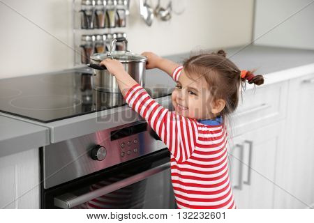 Little girl playing with electric stove in kitchen