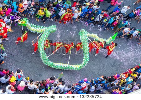 Binh Duong, Vietnam - February 22nd, 2016: Festival dragon dance Chinese Lantern with blue dragon winding from control martial arts practitioners across street to cheers tourists around in Binh Duong, Vietnam