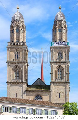 Zurich Switzerland - 25 May 2016: towers of the Grossmunster cathedral with a banner which is a part of the promotion devoted to the World Refugee Day on the 20th of June arranged by aid organization of Evangelic Churches of Switzerland (German: Hilfswerk